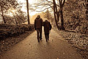 persone anziane in cammino nel bosco in cerca di una badante